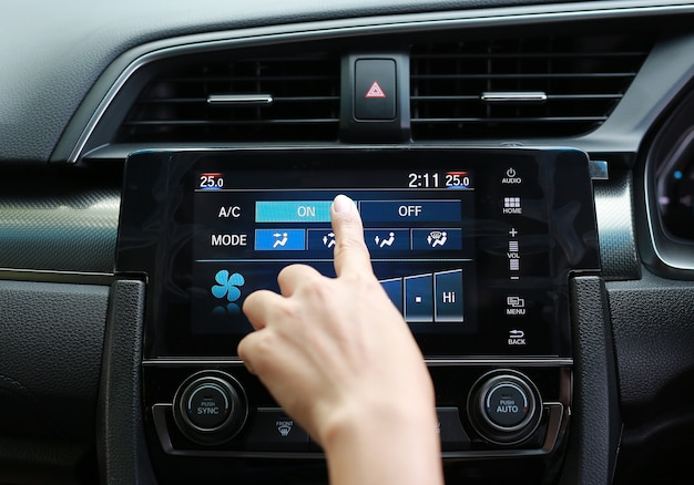 Palec naciskając przycisk na klimatyzatorze w desce rozdzielczej nowoczesnego samochodu