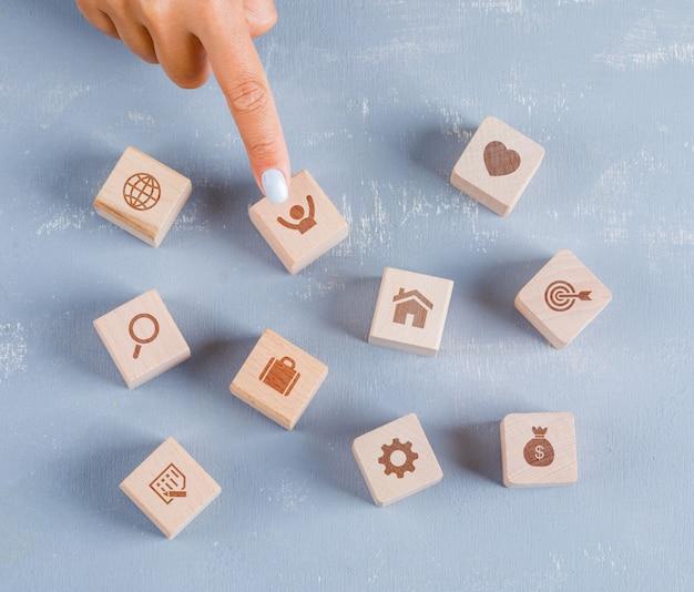 Palec pokazujący drewnianą kostkę