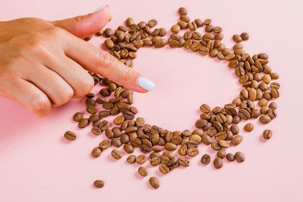 Palec pokazujący przerwę w sercu ziaren kawy