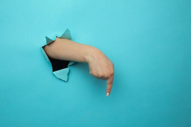 Palec skierowany w dół przez podartą ścianę z niebieskiego papieru. gesty dłoni wskazujące kierunek