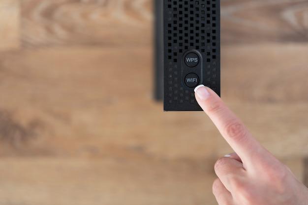Palec w pobliżu przycisku wifi routera wifi