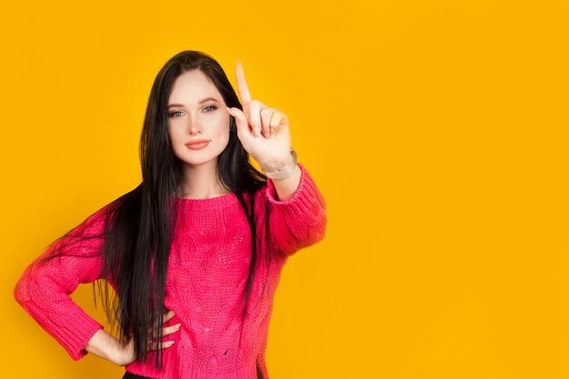 Palec wskazujący w górę, dziewczyna trzyma na żółtej ścianie, z miejsca kopiowania. pomyśl o cennych wskazówkach, pierwszym kroku lub pierwszym działaniu, ważnej informacji.