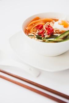 Pałeczki do jedzenia w zbliżeniu w pobliżu azjatyckiej zupy