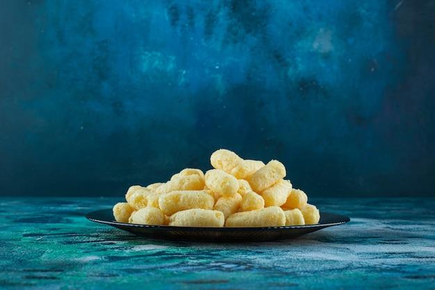Pałeczki kukurydzy cukrowej na szklanym talerzu na niebieskiej powierzchni