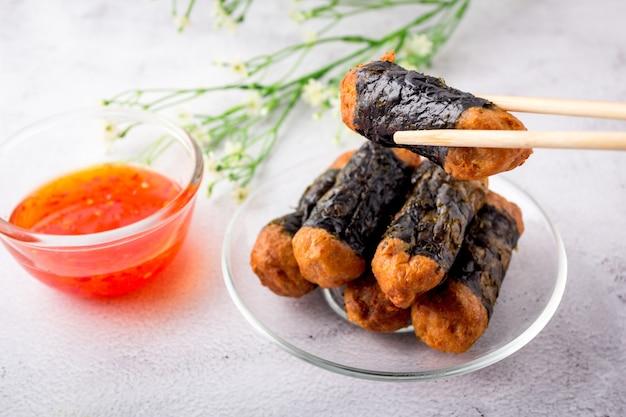 Pałeczki trzymają seaweed chicken roll are. roladki z kurczaka z wodorostów są układane na szklanym talerzu ze słodkimi sosami chilli.
