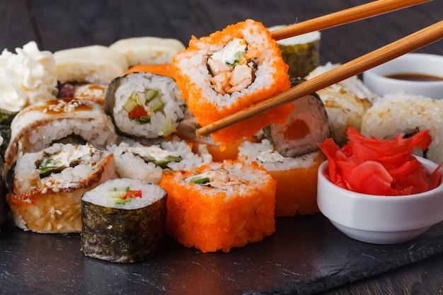 Pałeczki trzymające roll philadelphia z marynowanym ryżem, serem philadelphia