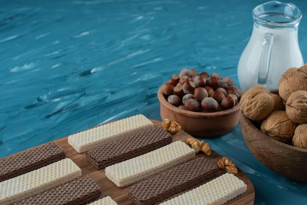 Pałeczki waflowe ze szklanym dzbankiem mleka i orzechami włoskimi z orzechami makadamia