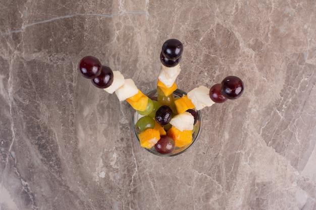 Pałeczki z mieszanych owoców ze szkła na marmurowym stole.