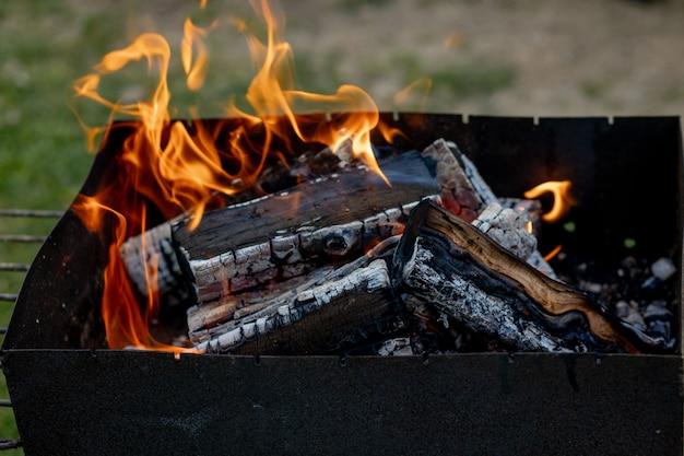Palenie drewna opałowego w grillu. przytulne wiosenne lub letnie wieczory przy kominku przy grillu