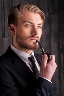 Palenie fajki. portret przystojnego młodego mężczyzny w formalwear, palącego fajkę i odwracającego wzrok