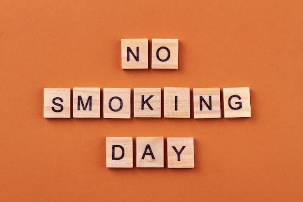 Palenie jest niezdrowym nawykiem. walka ze złym nawykiem. drewniane klocki z literami na białym tle na pomarańczowym tle.