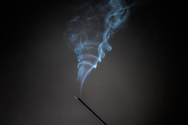 Palenie kadzidełek z unoszącym się relaksującym dymem.