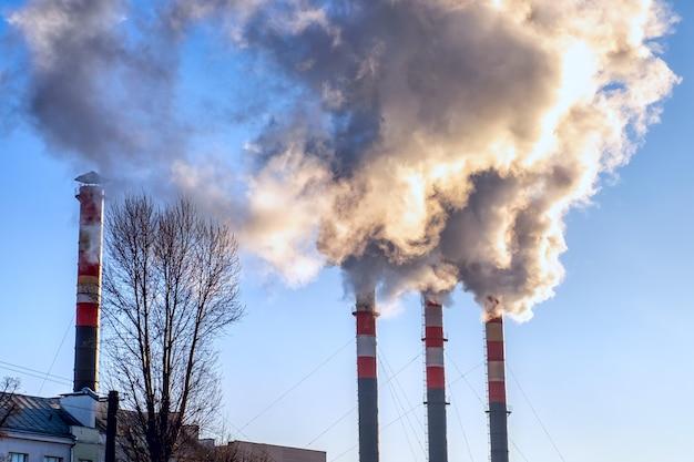 Palenie kominów na tle zimowego nieba. sezon grzewczy. widok na szczyty kominów stacji termicznej z kłębami dymu.