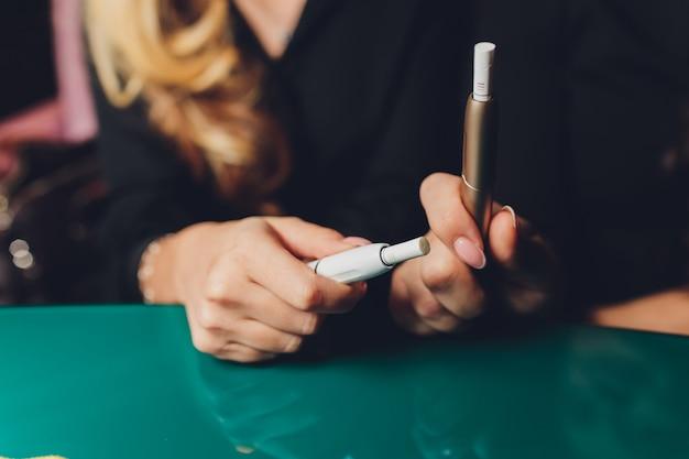 Palenie nowoczesnego hybrydowego urządzenia papierosowego technologia wyrobu tytoniowego niepalącego.