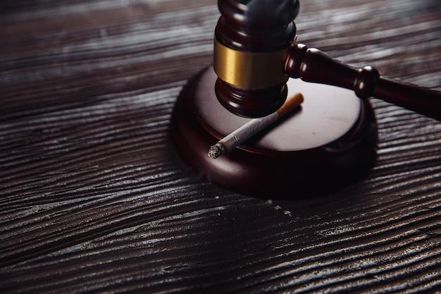 Palenie papierosów i drewniany młotek sędzia z bliska. niebezpieczny nawyk