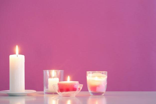 Palenie świec na różowym tle