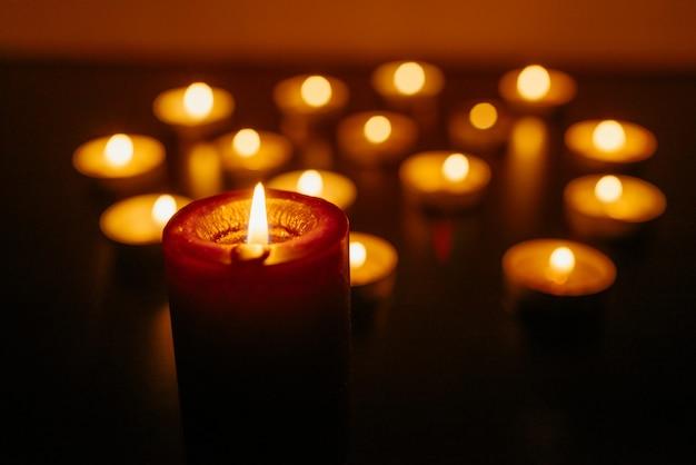 Palenie świec Niewielka Głębokość Pola. Wiele świeczek Bożonarodzeniowych Płonących W Nocy. Wiele Płomieni świec świecących. Premium Zdjęcia