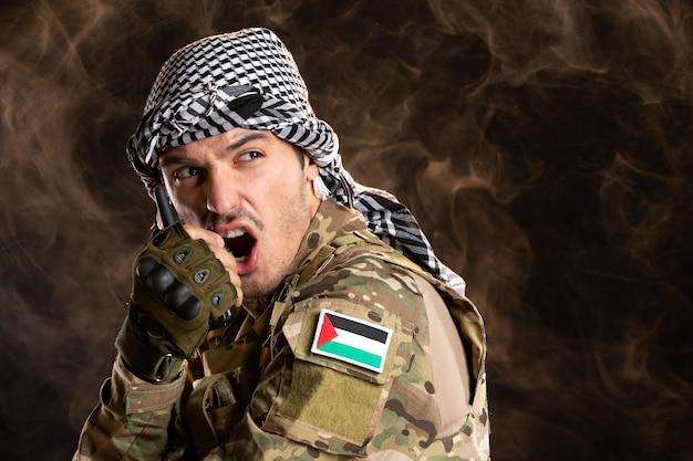 Palestyński żołnierz rozmawiający przez radioodbiornik na ciemnej ścianie
