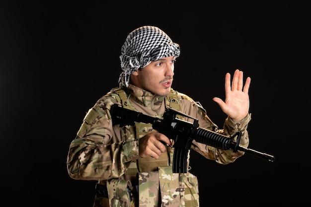 Palestyński żołnierz w kamuflażu walczący z karabinem maszynowym na czarnej ścianie
