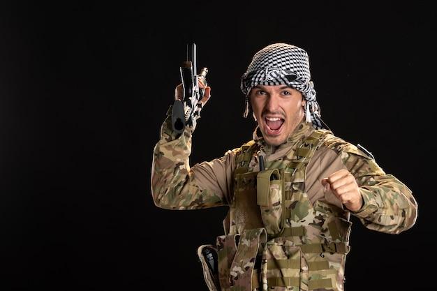 Palestyński żołnierz w kamuflażu z karabinem maszynowym na czarnym biurku wojenny czołg palestyński