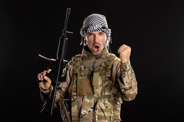 Palestyński żołnierz w wojskowym mundurze z karabinem na ciemnej ścianie