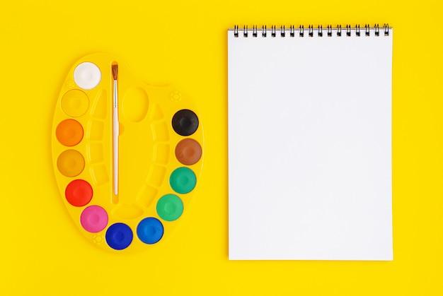 Paleta akwareli i makieta biały scetchbook na żółtym tle. leżał na płasko, szablon.