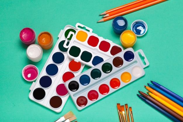 Paleta artystyczna z kolorowymi farbami, ołówkami i pędzlami