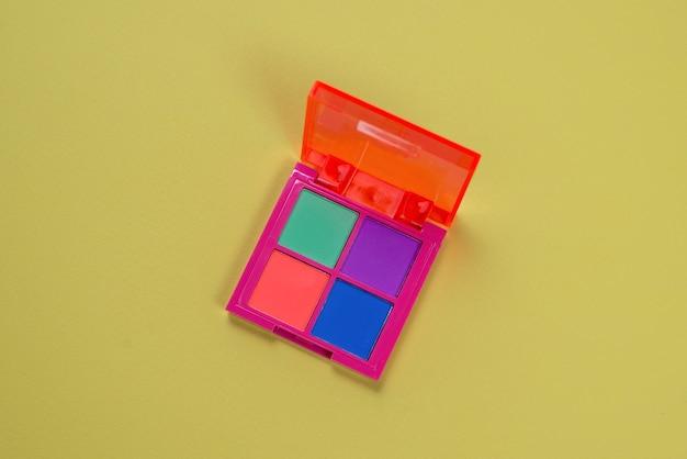Paleta cieni do powiek fioletowy, zielony, pomarańczowy i niebieski na zielonym tle. makijaż. neonowe kolory.