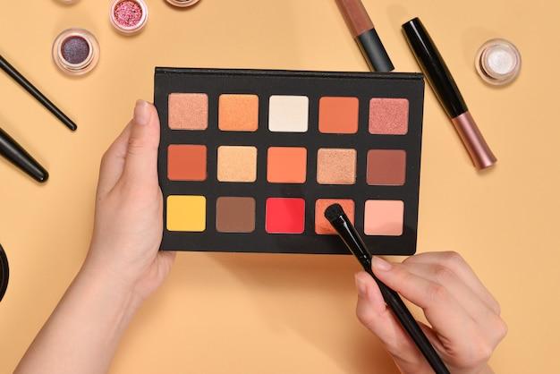 Paleta cieni do powiek na ręce kobiety. profesjonalne produkty do makijażu z kosmetykami kosmetycznymi