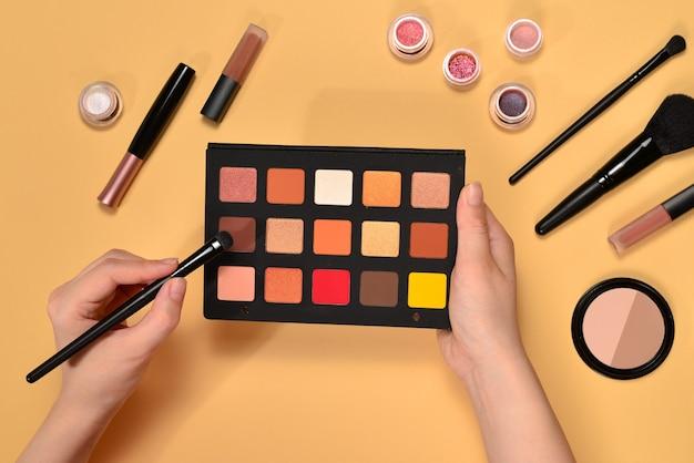 Paleta cieni do powiek na ręce kobiety. profesjonalne produkty do makijażu zawierające kosmetyki, podkład, szminkę, cienie do powiek, pędzle i narzędzia.