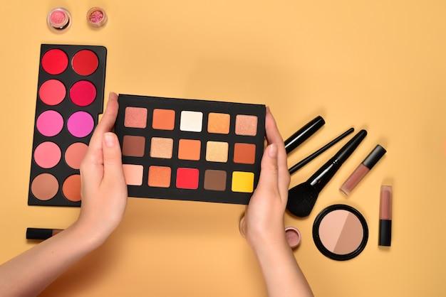 Paleta cieni do powiek na rękę kobiety. profesjonalne produkty do makijażu zawierające kosmetyki kosmetyczne, podkłady, szminki, cienie do powiek, pędzle i narzędzia.
