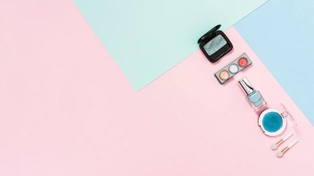 Paleta cieni do powiek; proszek kompaktowy; butelka do paznokci i pędzel na pastelowym tle