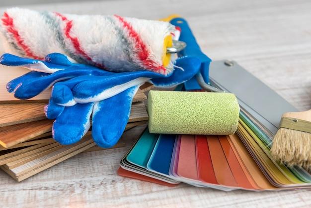 Paleta farb narzędziowych i pędzel, niebieskie rękawiczki do warsztatu naprawczego. tło pracy w domu