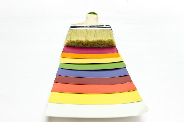 Paleta kolorów i pędzel, przewodnik po katalogu próbek farb. paleta do wyboru farby do remontu domu.