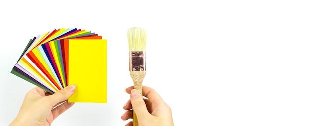 Paleta kolorów kart z pędzlem w ręku na białym tle.
