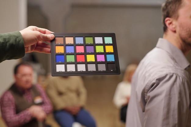 Paleta kolorów trzymana przez mężczyznę przeciwko pacjentom psychologa siedzącym na krzesłach