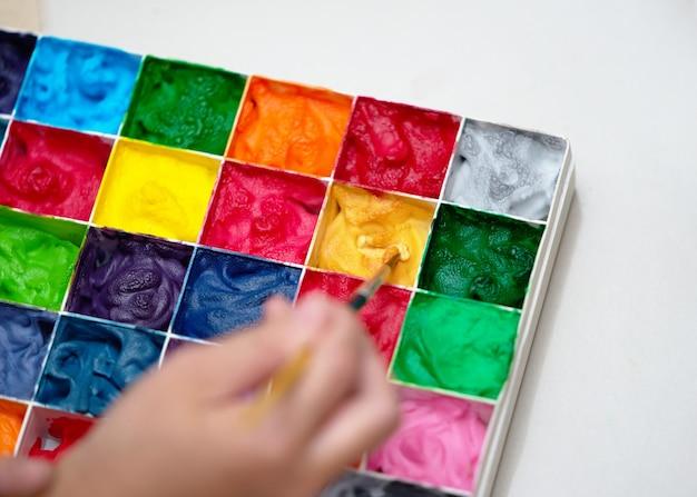 Paleta kolorów w kształcie kwadratu, zamknięta, z pędzlem do rysowania z rozmyciem dłoni