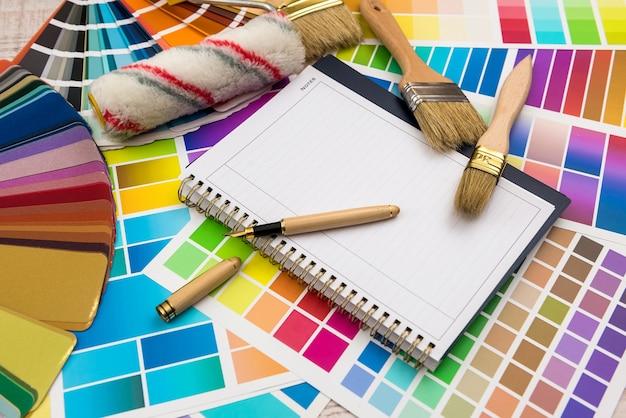 Paleta kolorów z narzędziami do malowania i pustym notatnikiem do projektowania