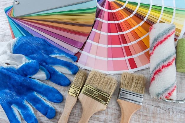 Paleta narzędziowa i pędzel, niebieskie rękawiczki do naprawy. tło pracy domowej