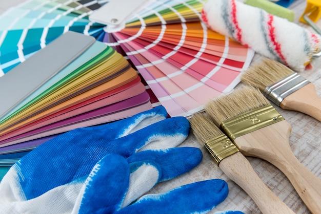 Paleta próbników kolorów z pędzlem i rękawiczkami do aranżacji wnętrz. cały sprzęt do remontu domu.