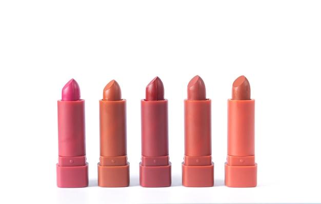 Paleta szminek moda w kolorach czerwonym, brązowym i różowym na białym tle, zdjęcie studyjne. piękny makijaż lub koncepcja sprzedaży kosmetyków