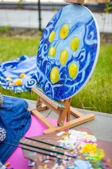 Paleta z wielokolorowymi farbami i pędzlami kobieta maluje obraz