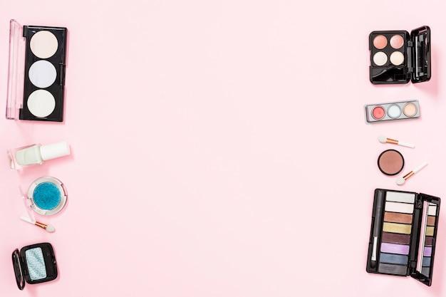Palety cieni do powiek z butelką lakieru do paznokci na różowym tle