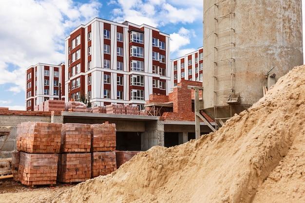 Palety z cegłami i kupa piasku na budowie