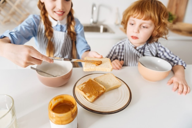 Paliwo na dziś. podekscytowane jasne, urocze dzieciaki jedzące pierwszy posiłek dnia, siedząc w kuchni przed pójściem do szkoły
