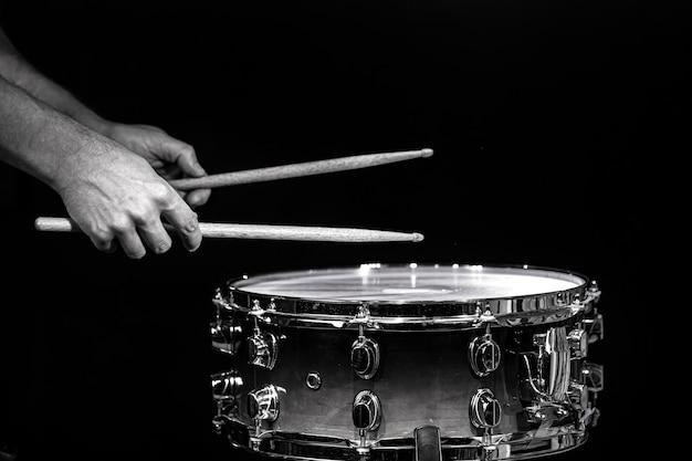 Pałki perkusyjne uderzając w werbel z rozpryskiwania wody na czarnym tle w oświetleniu studyjnym. czarny i biały. zdjęcie w ruchu.