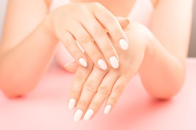 Palma żeńska w średnim wieku. piękny manicure glamour. dbaj o dłonie i paznokcie, czystą skórę. profesjonalny manicure w gabinecie kosmetycznym. higiena i pielęgnacja dłoni. koncepcja branży kosmetycznej.