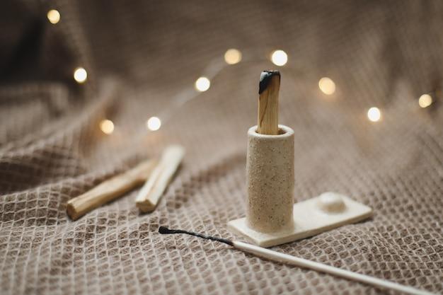 Palo santo drewniany kij płonący z dymem w pięknym świeczniku w przytulny wieczór w domu