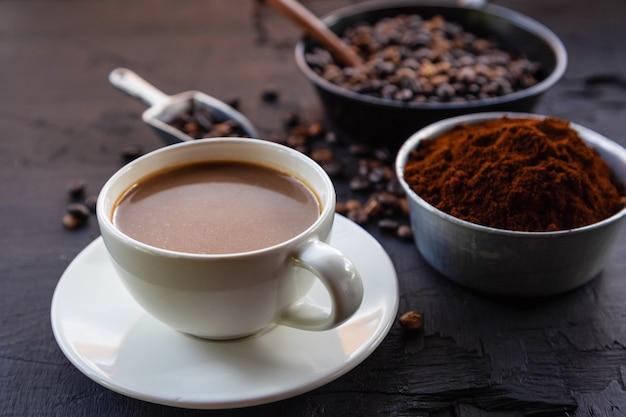 Palona kawa ziarnista z kawą mieloną i filiżankami.