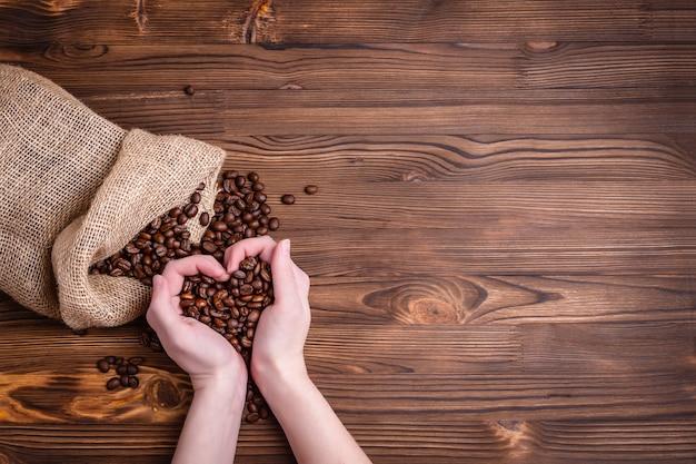 Palone ziarna kawy budzą się z jutowej torby na starym drewnianym stole. zbliżenie. kobiece dłonie złożone w kształcie serca, copyspace.